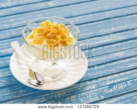 Pear with natural yoghurt corn flakes and honey - a delicious dessert breakfast or snack . On a blue wooden background
