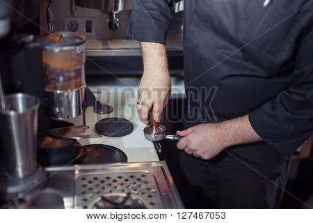 Close-up of barista grinding coffee.Barista prepares cappuccino in his coffee shop. Close-up cup of coffee.