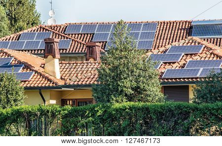 Photovoltaic solar panels on the tiled roofs of residential homes providing alternate energy and electricity from the sun