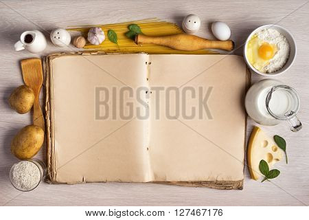 vintage cook book and ingredients for the food recipe around in a frame on the background of the table