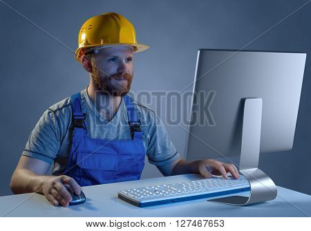 worker builder in helmet and uniform working at a computer, purchase in online store