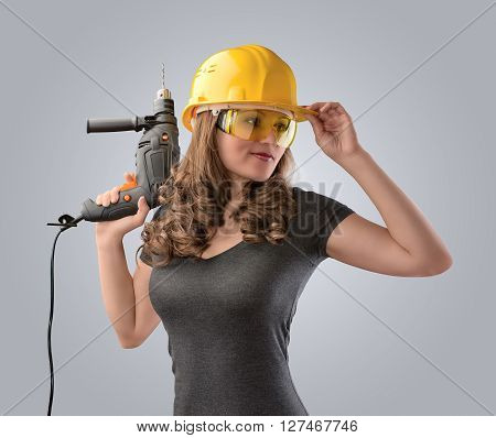 worker girl in a helmet with a drill on a gray background