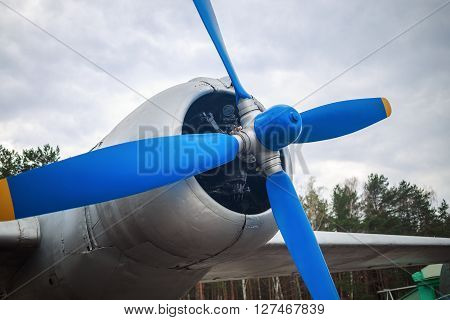 Closeup of propeller and engine of old vintage aircraft. Propeller of retro airplane. Selective focus on propeller.