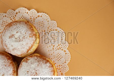 Delicious donuts with powdered sugar on napkin top view