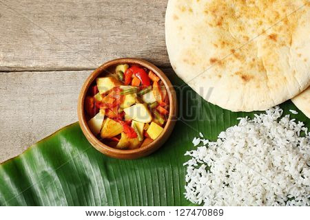 Boiled rice with vegetables and flat bread on banana leaf over wooden background