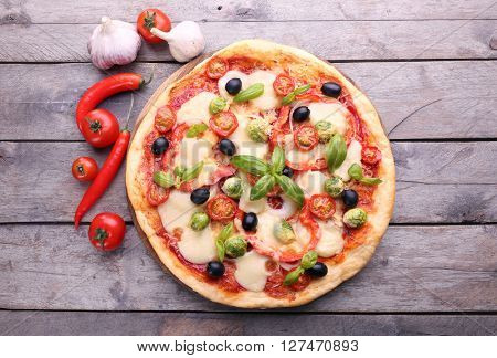 Delicious pizza with cheese and vegetables on wooden background