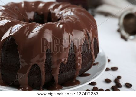 Ring chocolate cake with glaze in plate closeup