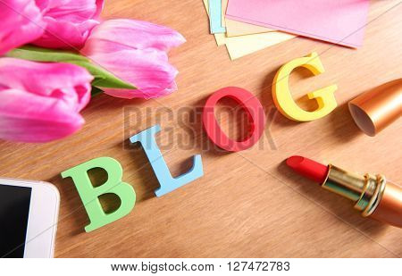 Word BLOG with mobile phone, lipstick and tulips on wooden background