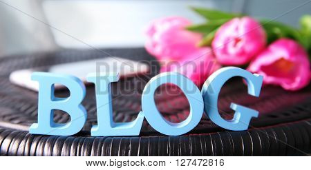 Word BLOG with mobile phone and fresh tulips on wicker chair closeup