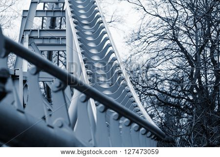 abstract curved steel structure of silvery color for an attraction in park under the open sky