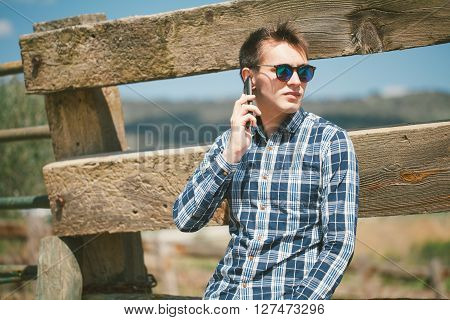 Young Man Calling By Phone In The Countryside.