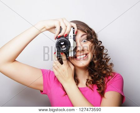 young pretty woman holding vintage camera