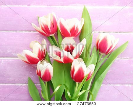 Bouquet of variegated tulips with cup of coffee on wooden background