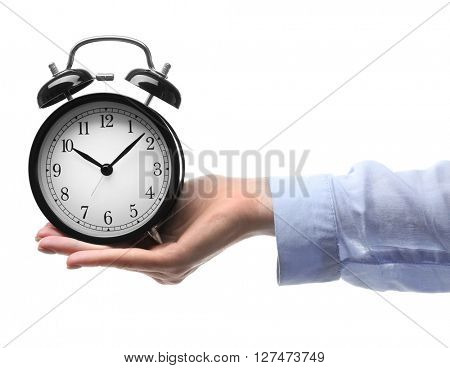 A retro alarm-clock on female hand, isolated on white