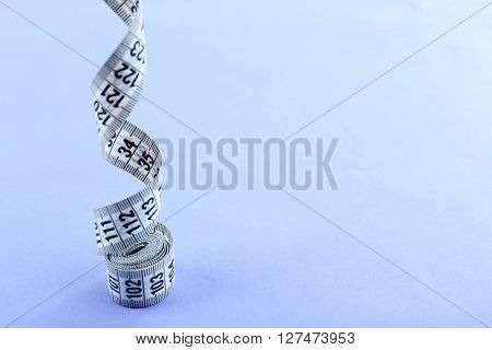 White measuring tape on a purple background