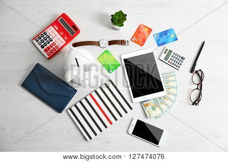 Piggy bank with tablet, credit cards and other accessories on wooden table, top view