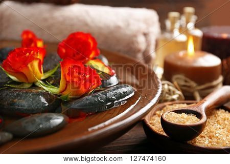 Spa wooden bowl with water, flowers and stones closeup