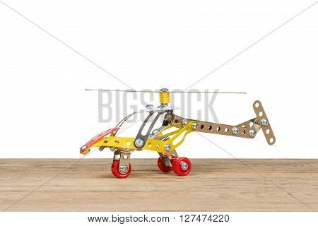 Children helicopter made of iron constructor standing on an old wooden table isolated on white background