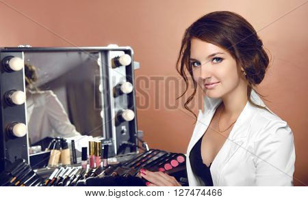 Beauty Makeup Artist Woman With Cosmetics By Mirror In Dressing Room. Attractive Female Face Portrai