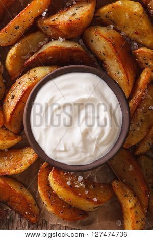 Baked Potato Wedges And Sauce Close-up On The Table. Vertical Top View
