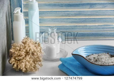 Salt in blue bowl with towel on bathroom table