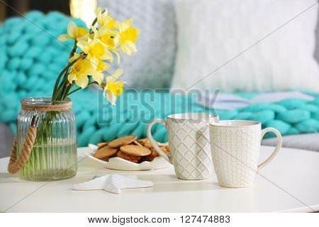 Cups with cookies and bouquet of narcissus on table indoors
