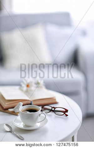 White cup of the coffee and a book on a table  in a light room..