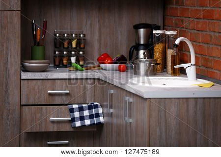 Modern kitchen furniture with sink, coffee maker and utensils