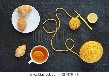 Lemon tea, yellow crocheting and croissants on a plate.