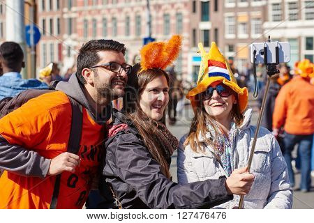 AMSTERDAM, NETHERLANDS on APRIL 26, 2015. City natives and tourists celebrate Queen's Day or King's day, Dutch annual national holiday, in the streets of Amsterdam, Holland