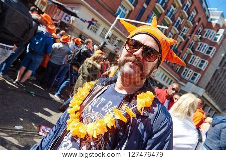 AMSTERDAM, NETHERLANDS on APRIL 26, 2015. Portrait of male city native tourist celebrating Queen's Day or King's day, Dutch annual national holiday, in the streets of Amsterdam, Holland