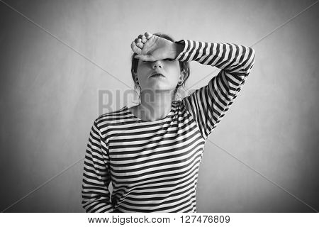 Tired woman in a sailor's striped vest covering her face with a hand. Retouched image. Vignette is added.