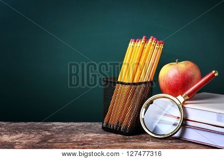 Set of pencils in metal holder, magnifier and apple on blackboard background