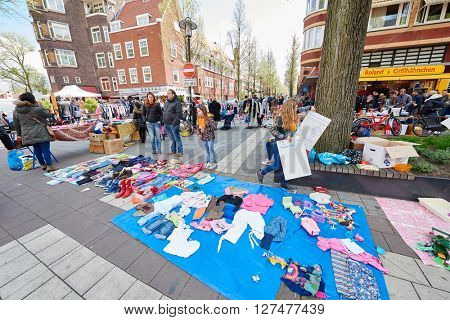 AMSTERDAM, NETHERLANDS on APRIL 26, 2015. Flea market for natives and tourists during Queen's Day or King's day, Dutch annual national holiday, in the street of Amsterdam, Holland