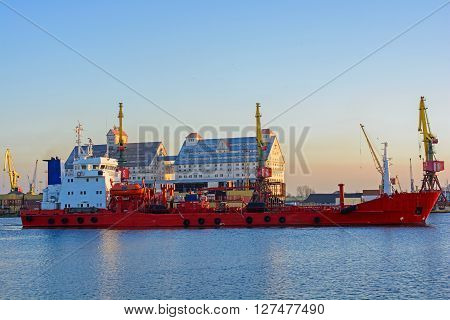 Commercial docks at sunset with a ship and cranes. Sea port