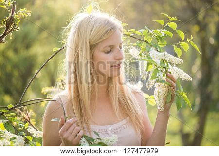 Portrait of young woman smiling in the flowered garden in the spring time.. Girl dressed in white like a bride.