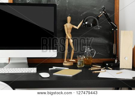 Desktop with computer monitor and other items against blackboard background