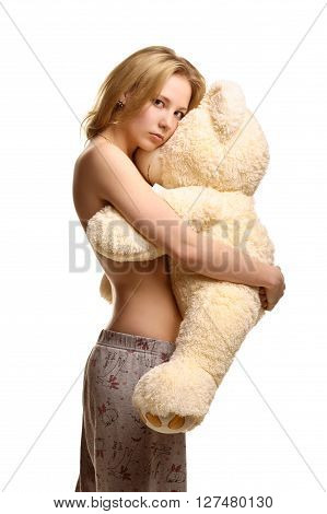 Concept: infantilism, childish, sadness, happiness. Girl in pijamas pants hugging giant plush bear toy isolated on white