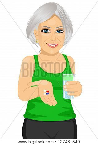 elderly woman holding glass of water taking vitamin pills isolated over white background