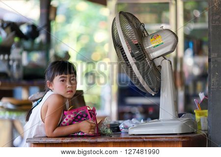 SAI YOK, THAILAND, JANUARY 21, 2016 : A Thai little girl is posing in her mother's shop drying her makeup with a fan  before going to a party in Sai Yok, Thailand