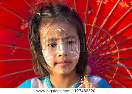 SANGHLABURI, THAILAND, JANUARY 23, 2016 : A Thai little girl holding traditional umbrella is posing on the Mon bridge in Sanghlaburi, Thailand