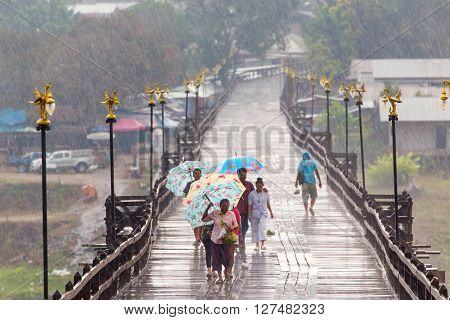 SANGHLABURI, THAILAND, JANUARY 24, 2016 : Thai family is walking under a heavy rain on the Mon bridge in Sanghlaburi, Thailand