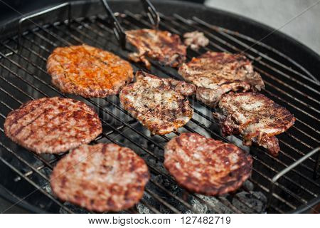 Man turning stakes and burgers on a BBQ oven.