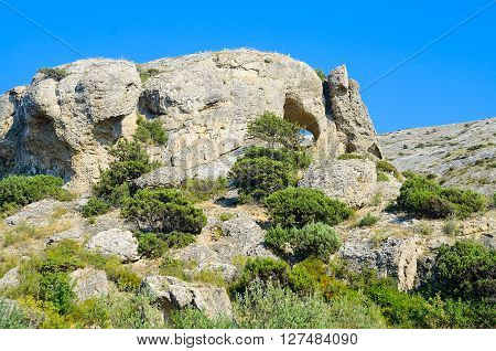 Mountain landscape with sparse greenery. Caves. Roast hot summer. Blue sky.