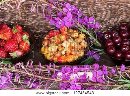 The photo shows ripe cherries , cloudberries, strawberries and flowers