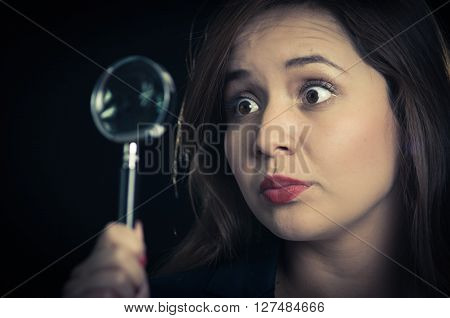 Young woman holding magnifying glass in front of eye and looking focused, black background.