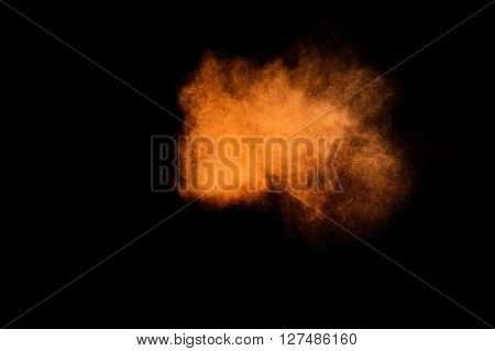 Abstract orange powder explosion on black background. Paint Holi.