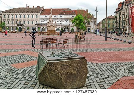 TIMISOARA ROMANIA - APRIL 25 2016: View of the Liberty-Square in Timisoara Romania with 3 principal element: Old bronze map a modernist metal statue and old plague statue.