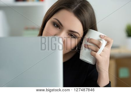 Tired female employee at workplace in office holding cup of tea. Sleepy worker early in the morning after late night work. Overworking making mistake stress termination or depression concept