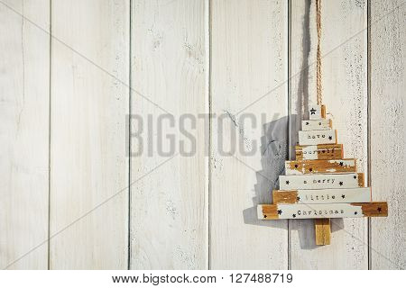 Wooden decorative tree with white shirts hanging on a wooden board.